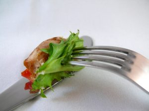 knife and fork with lettuce and tomatoe