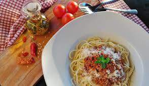 bowl of spagetti with tomatoes and spices on the table