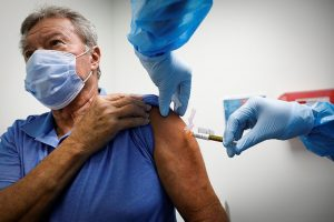 older person getting vaccine shot